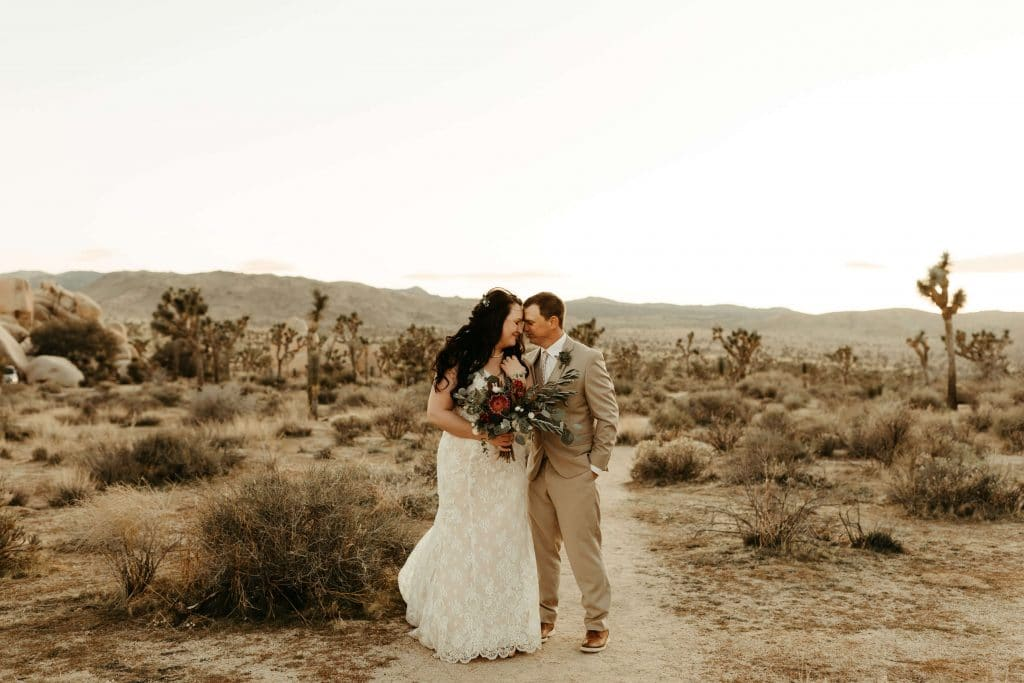 Joshua Tree Elopement at sunset. Bride with faux fur and dark red bouquet