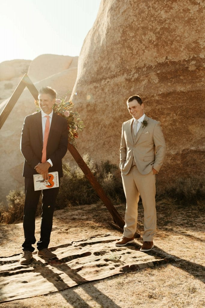Groom waits in front of triangle arch at Joshua Tree National Park