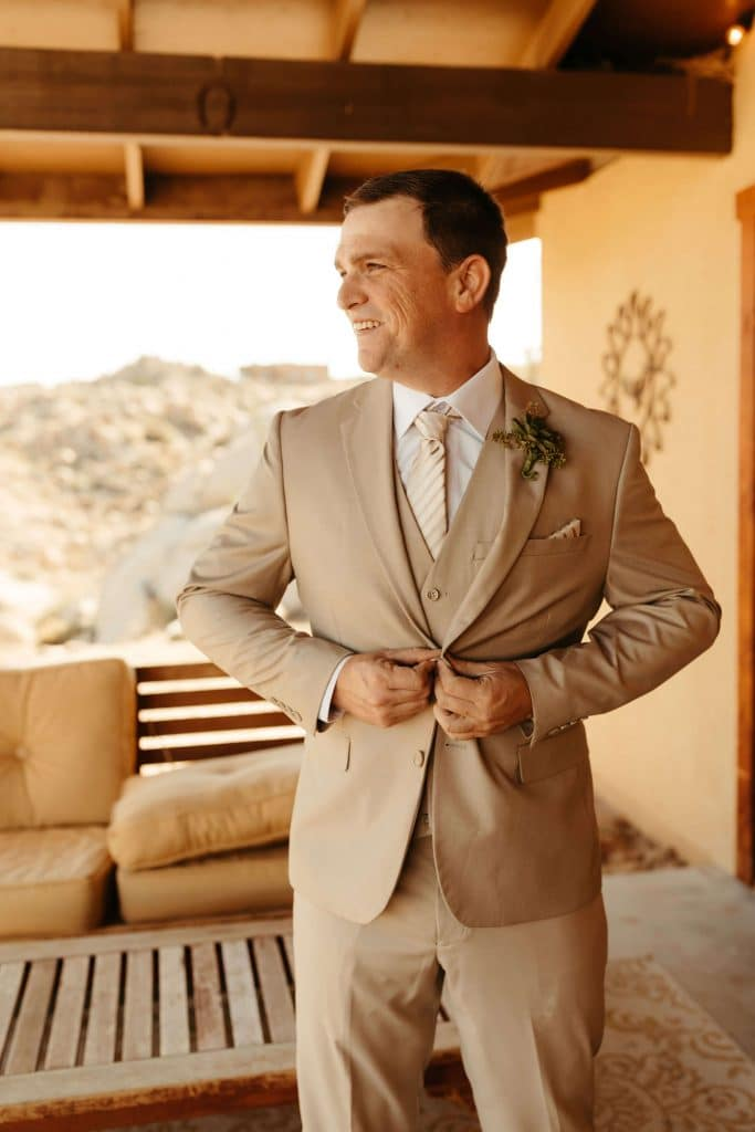 Groom in beige suit with succulent boutonniere