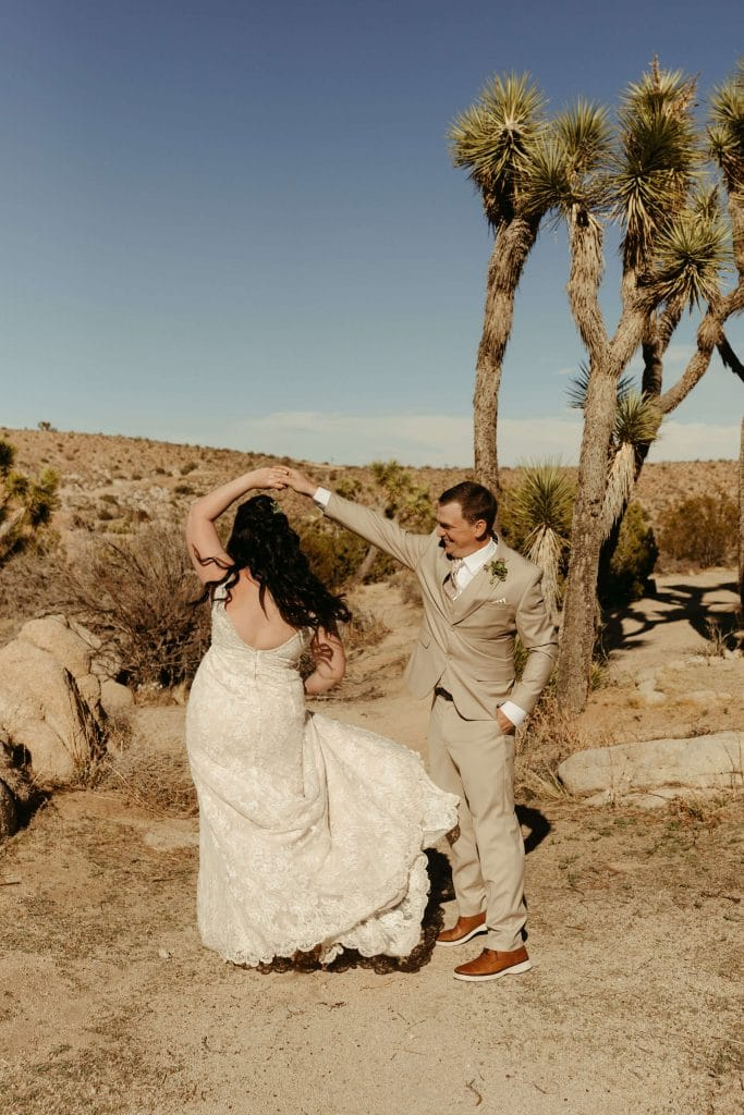 Bride and groom dance in desert at Joshua Tree National Park