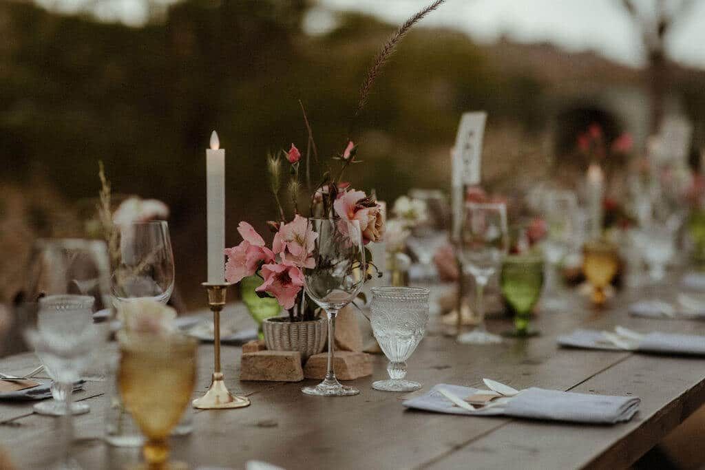 Long table with green and amber glasses and modern minimalist florals