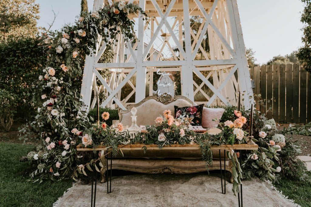 Edgy boho wedding sweetheart table with floral half moon arch