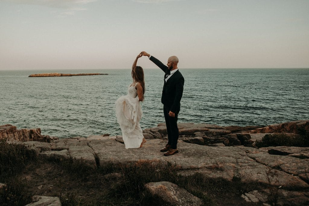 A couple dancing on the sea cliff after their intimate wedding in Acadia National Park
