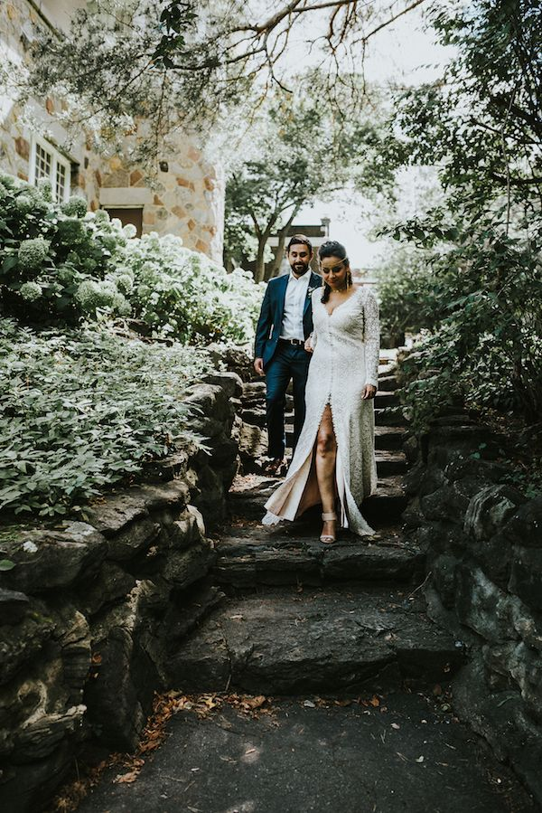 bride in slit dress walks down steps with groom in navy suit