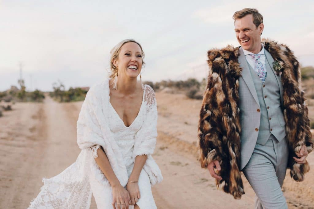 Bride and groom laugh with faux fur jackets on
