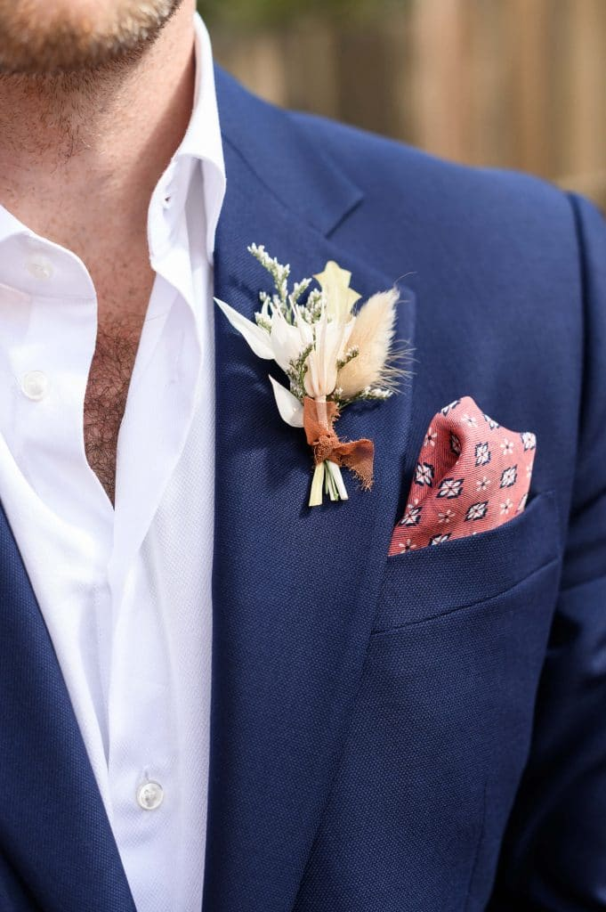 Dark blue groom suit with coral pocket square