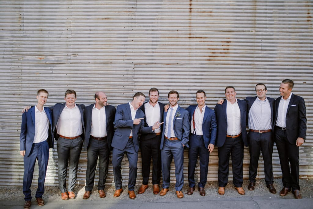 Groom and groomsmen in all navy blue suits and brown shoes