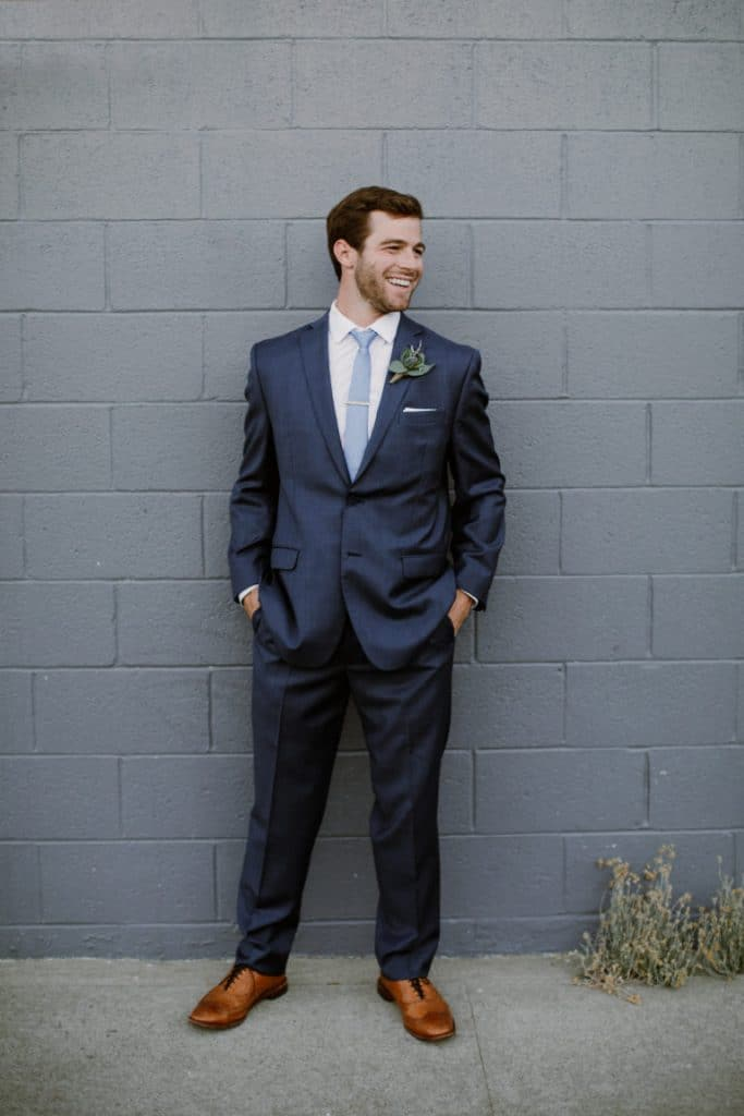 Groom suit in navy with blue tie and brown shoes