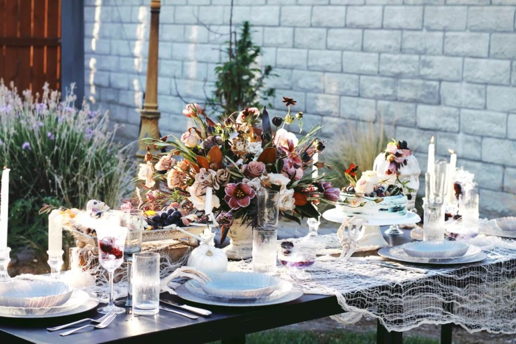 Neutral halloween table decor with blush florals and white skeleton hands.