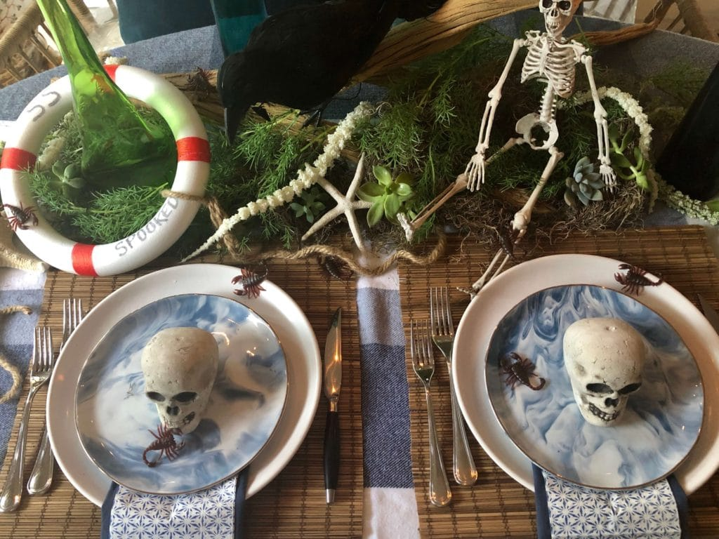 Table with two place settings of marbled navy and white plates on with scorpions and mini skulls.