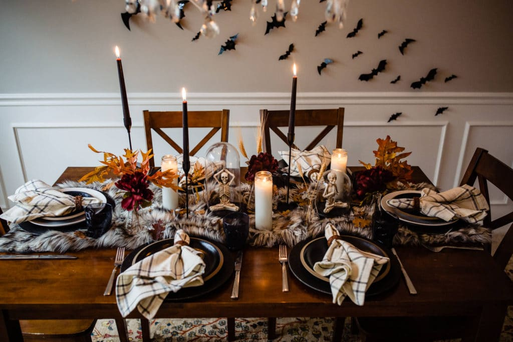 Halloween table decor on fur runner with six black and white place settings with artificial bats adhered to background.