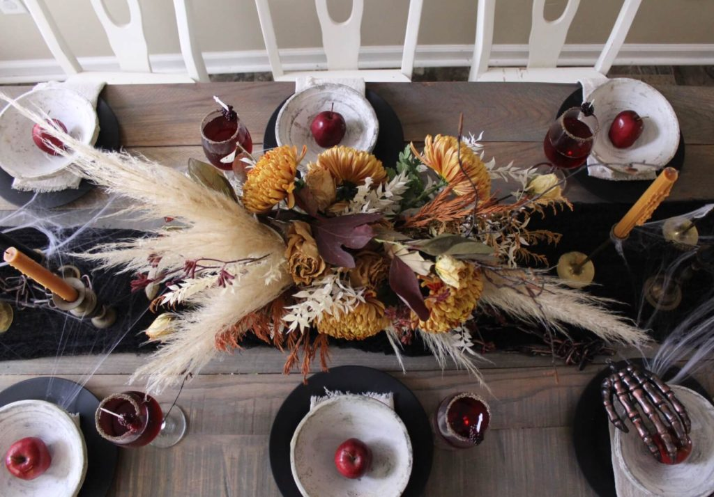 Yellow florals and pompous grass halloween centerpiece with six place settings of black plates and white stone bowls with a red apple in each bowl.