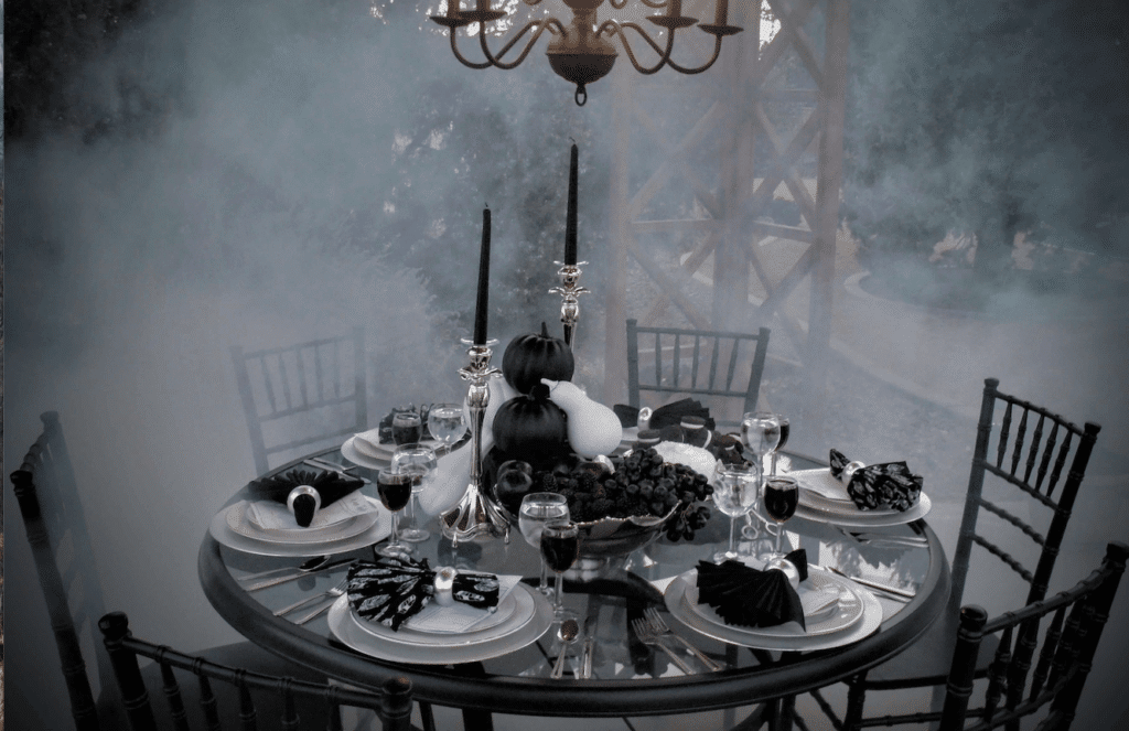 Six place settings on round table with black and white halloween table decor and pumpkins surrounded by fog.