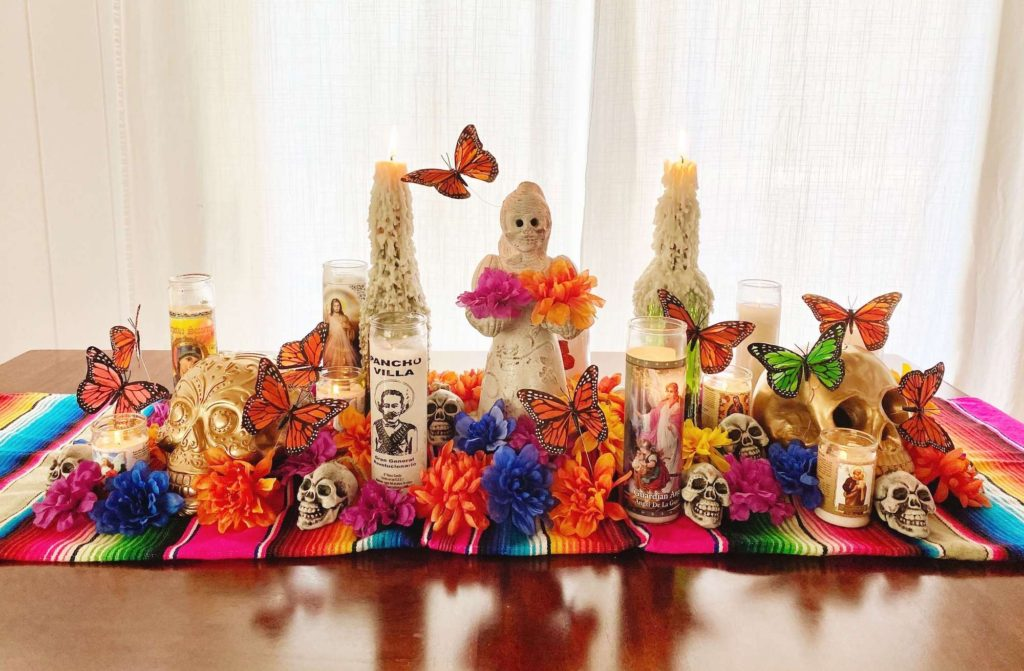 Colorful halloween table decor on rainbow runner with prayer candles and butterflies