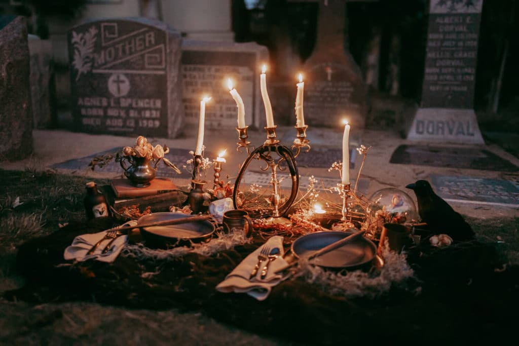 Halloween table decor on ground in graveyard with white tapered candles in gold candle holders.