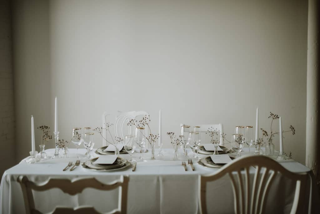 White and gold place settings with dried florals in mini vases on rectangular  table.