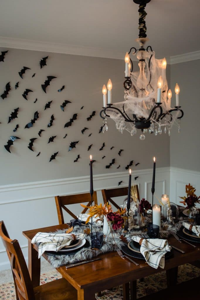 Halloween table setting with bats on wall and cobwebs on chandelier
