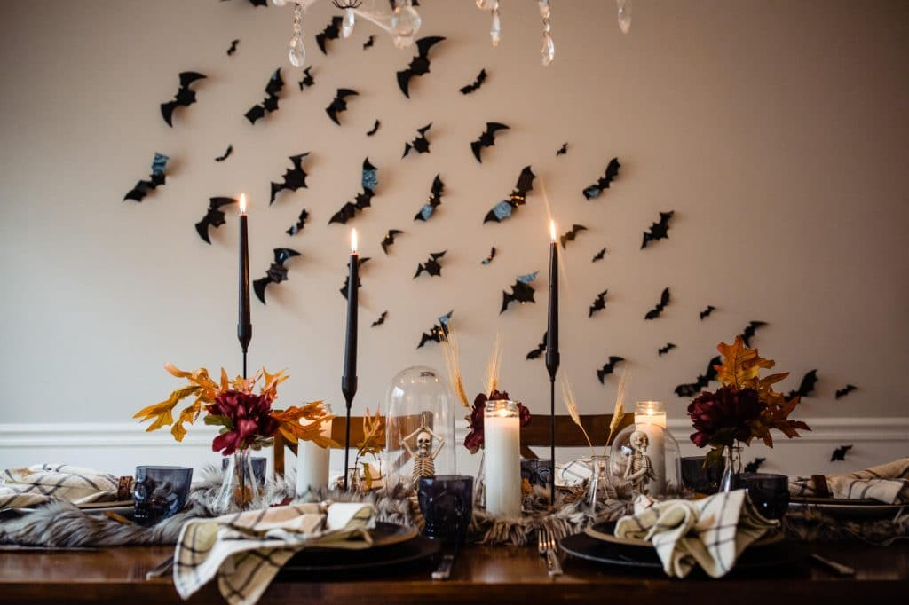 Bats on wall and table settings are decorated for halloween