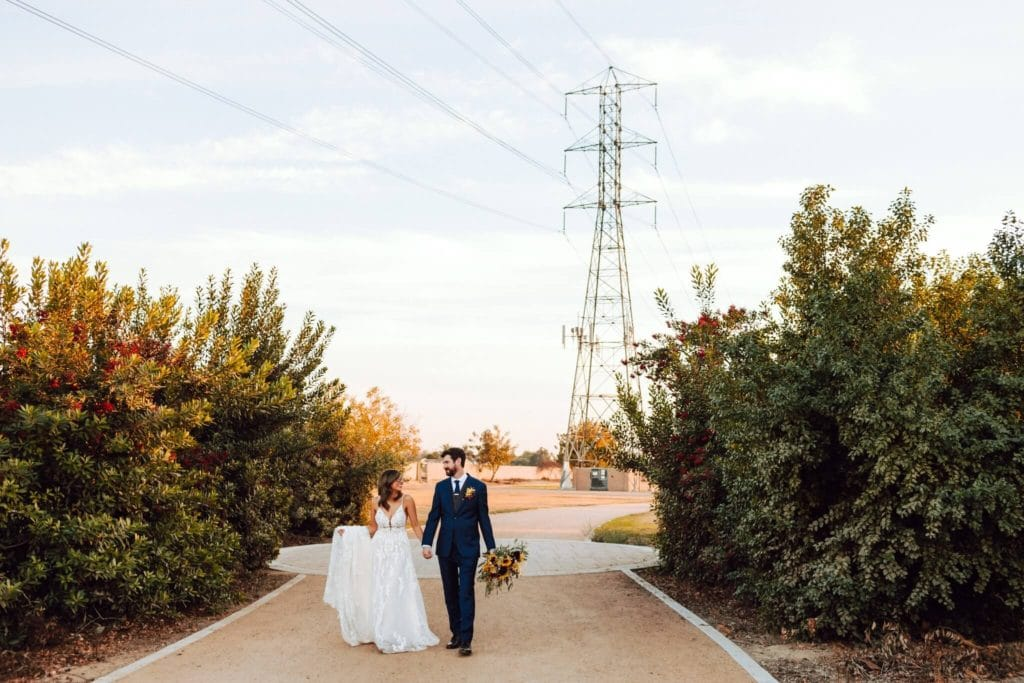 Bride and groom walking outside while holding hands and smiling