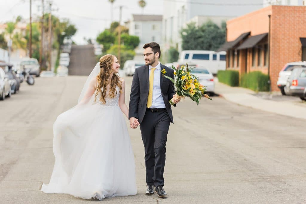 Bride and groom holding hands at spring wedding