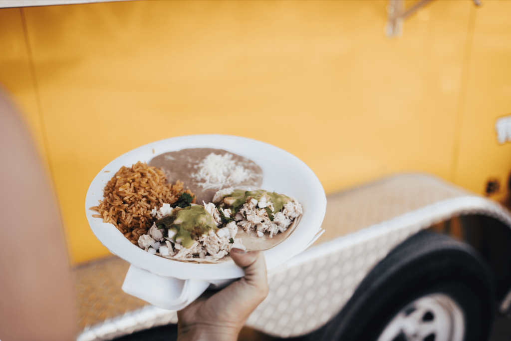 Plate of chicken street tacos, rice and refried beans for wedding welcome party food