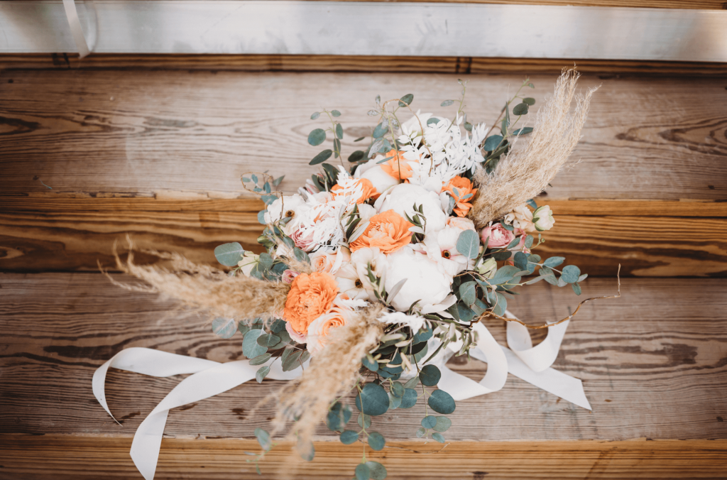 Boho bridal bouquet with orange and neutral flowers and pampas grass