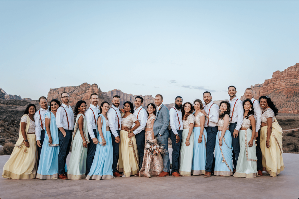 Bride and groom smiling with wedding party at Under Canvas Zion wedding