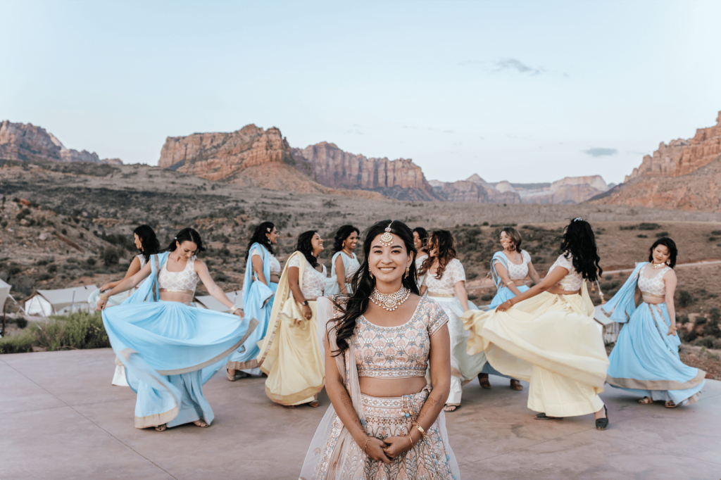 Bride smiling with bridesmaids twirling in colorful dresses