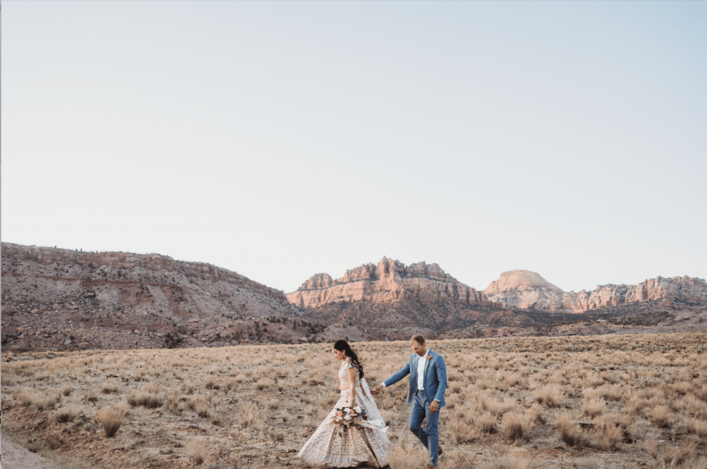 Bride and groom walking holding hands with mountain view at Under Canvas Zion