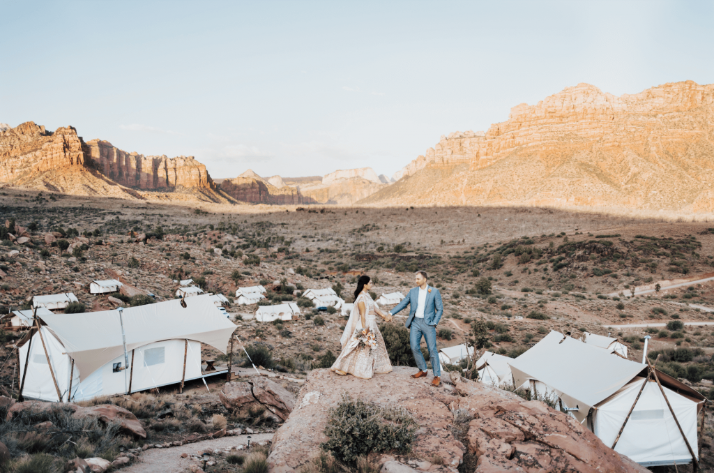 Bride and Groom on elevated rock ledge at glamping wedding at Under Canvas Zion
