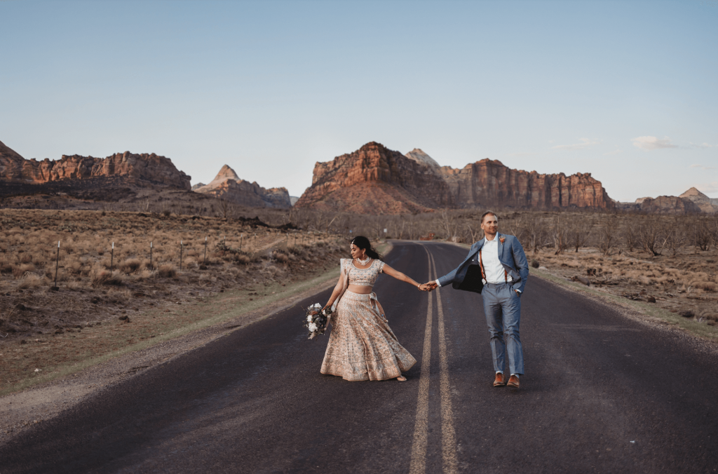 Bride and groom holding hands on road at Under Canvas Zion in Utah