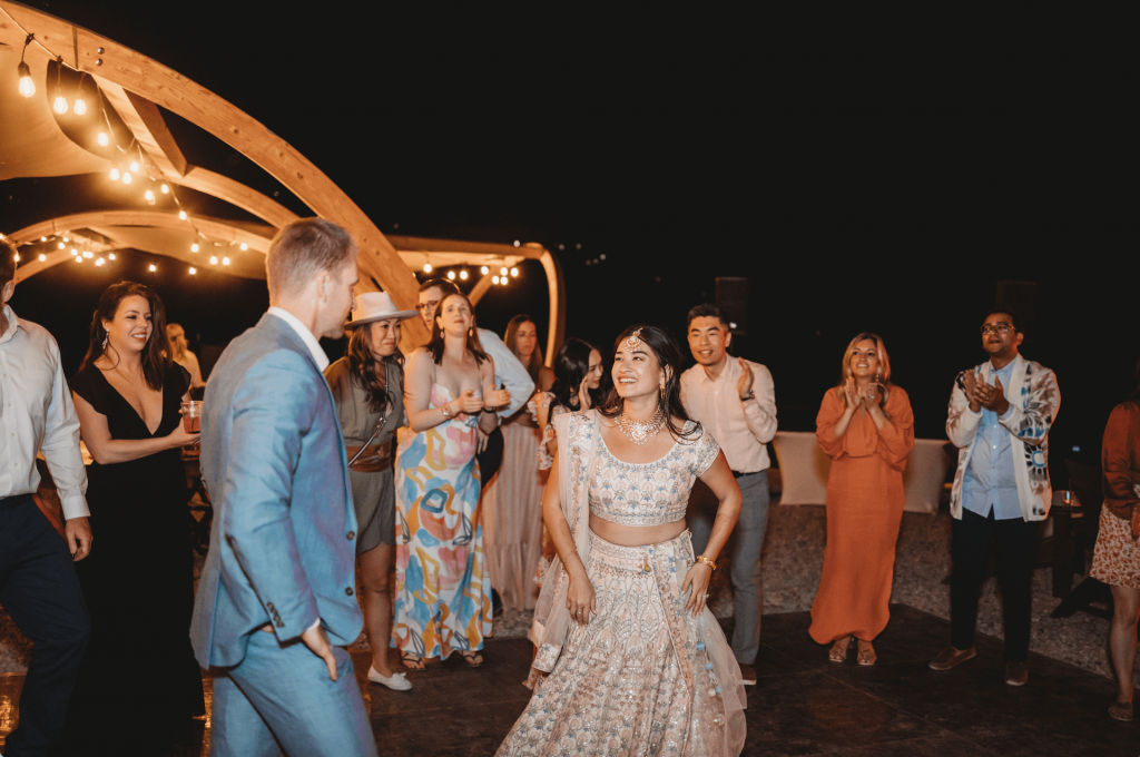 Bride and groom dancing surrounded by guests at Under Canvas wedding