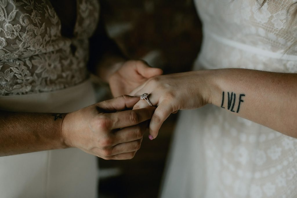 Brides with engagement ring at industrial boho elopement in Tennessee