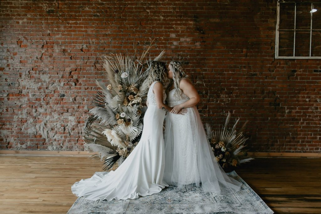 Brides kissing at intimate ceremony at industrial boho elopement at White Star Station Venue