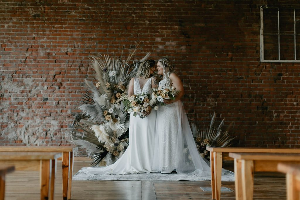 Brides smiling at boho ceremony at White Star Station venue in Tennessee
