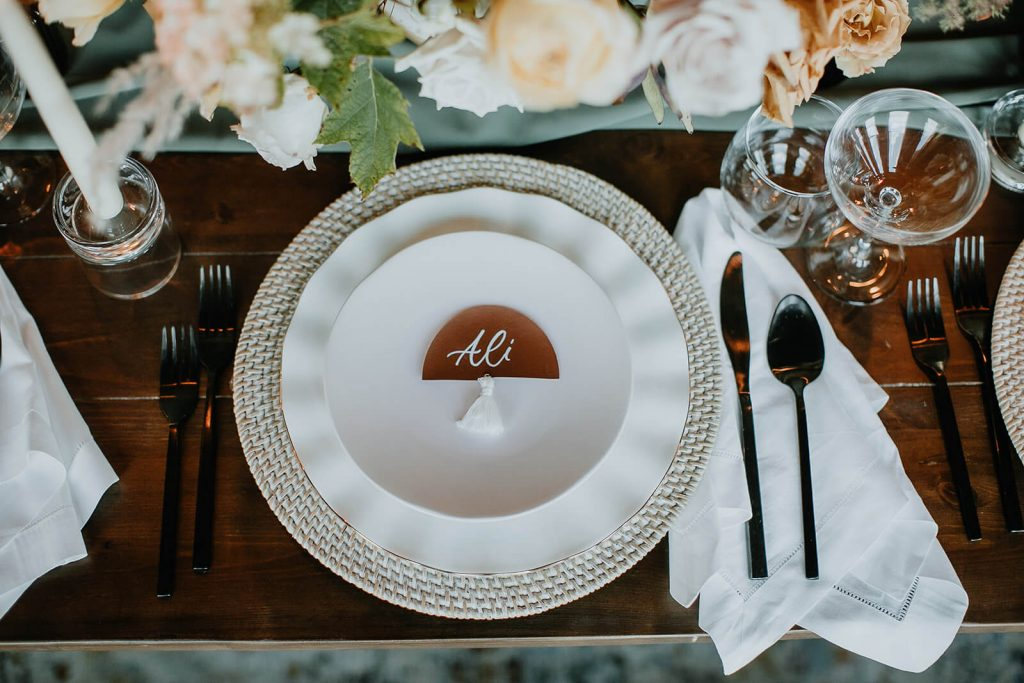 Layered neutral place setting with leather and tassel name card