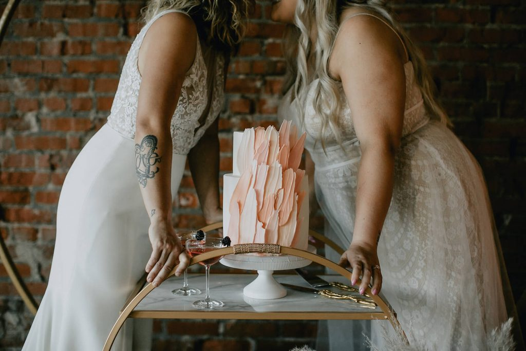 Brides kissing over modern two tiered wedding cake at industrial boho elopement in Tennessee