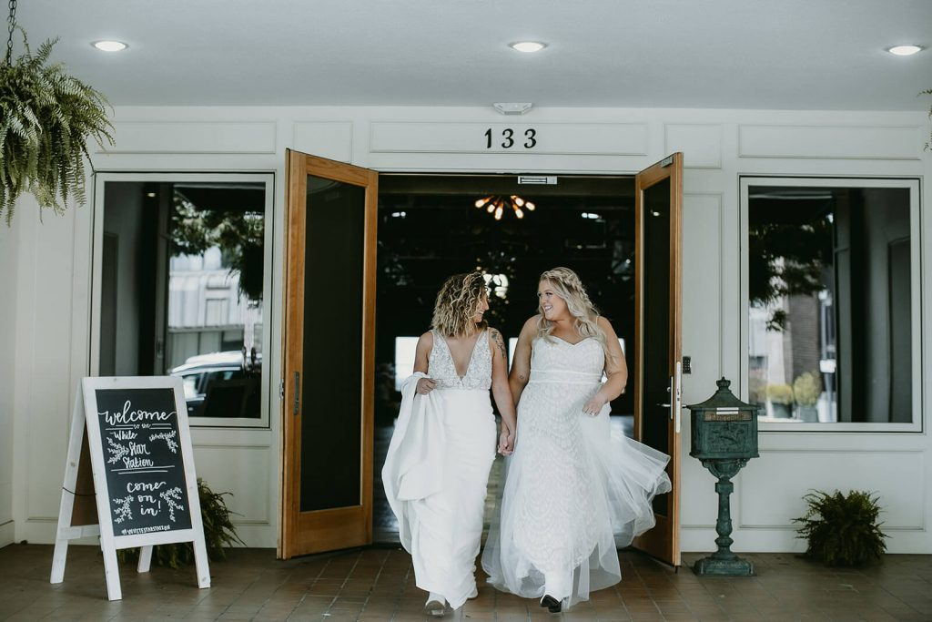 Brides walking out of boho industrial elopement at White Star Station venue in Tennessee