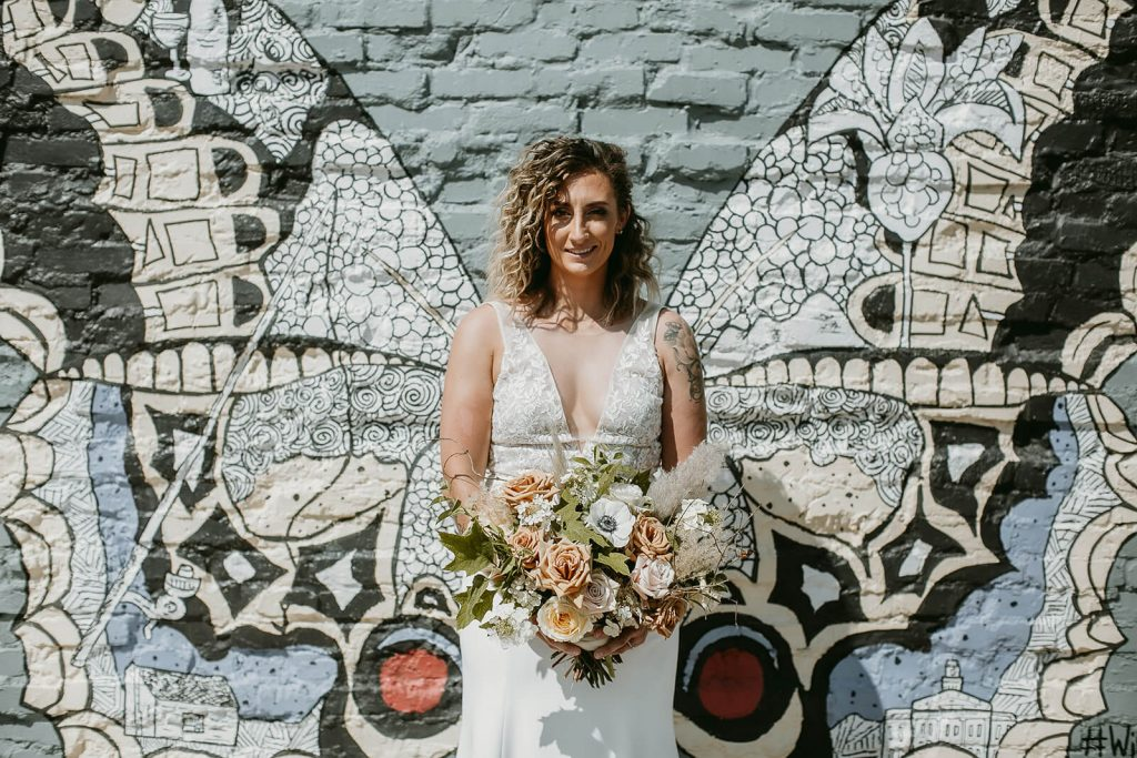 Boho bride in front of butterfly mural at White Star Station venue
