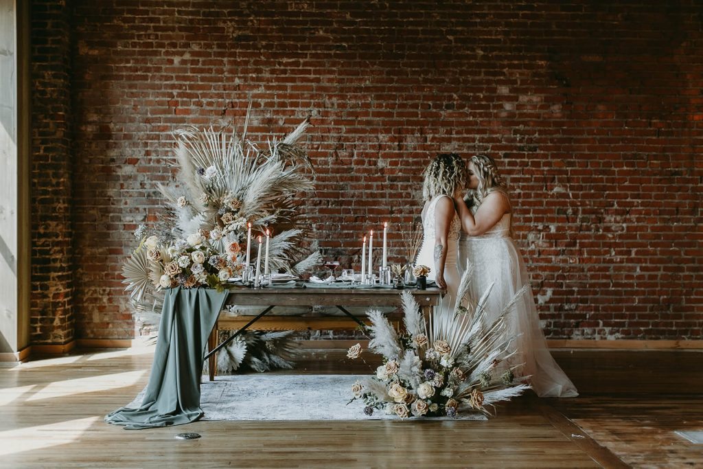 Brides kissing at sweetheart table for indoor industrial boho elopement in Tennessee