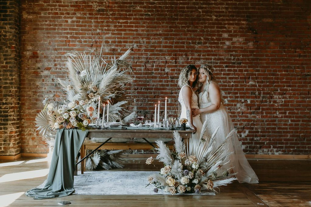 Brides standing beside sweetheart table decorated with boho details at industrial elopement