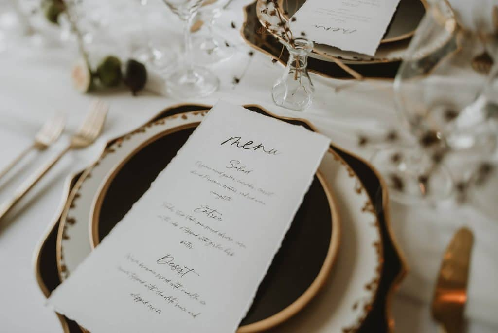 Layered black, white, and gold place setting with raw edge menu